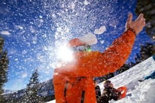 Epic man throw snow into air shot.